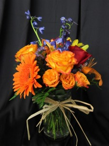 Fresh Flowers for Mother's Day featuring Circus Roses, Red Roses, Orange Gerbera Daisies and Blue Delphinium